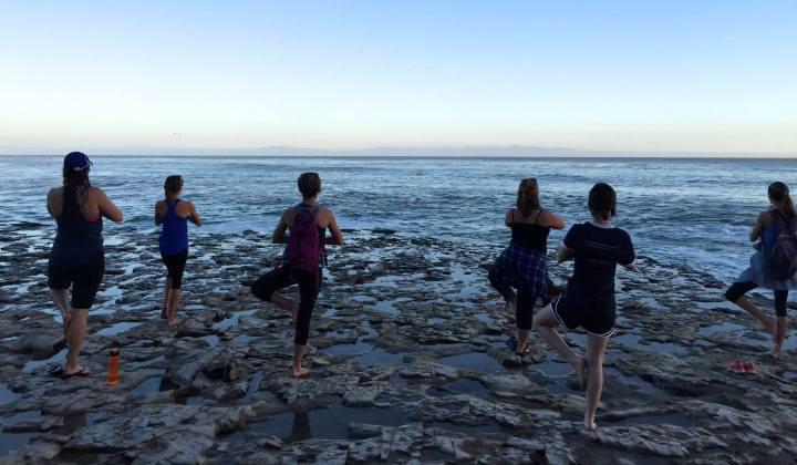 6 women doing yoga on the beach