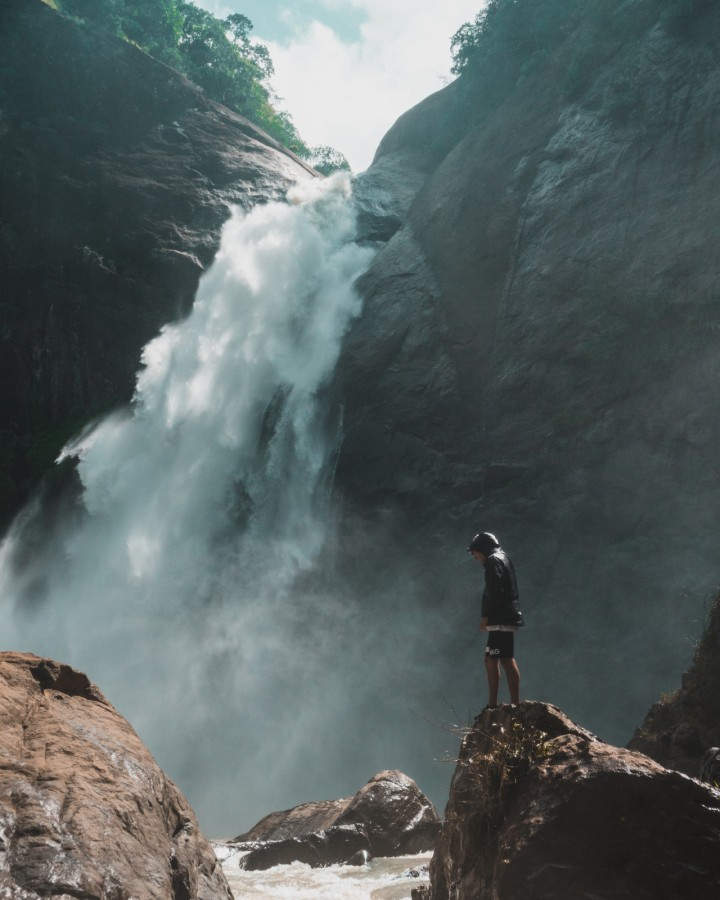 A person contemplatively standing next to a waterfall
