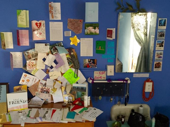 Picture of a wall and dresser with letters, cards, and notes