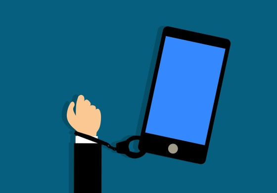 A hand chained to a smartphone