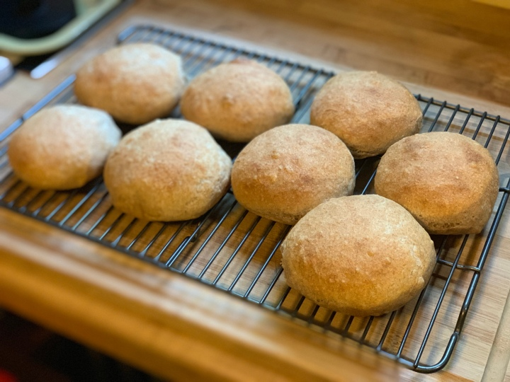 Eight buns of bread resting on cooling racks