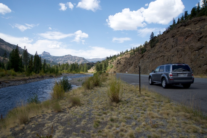 A car parked along a river in Yellowstone National Park indicating a road trip.