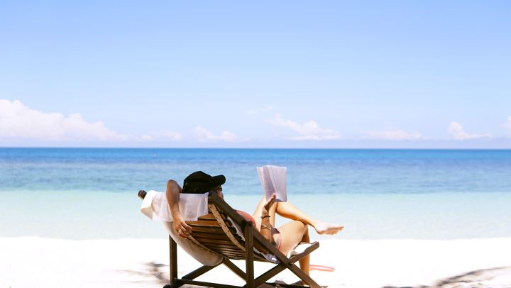 Woman sitting on brown wooden beach chair reading