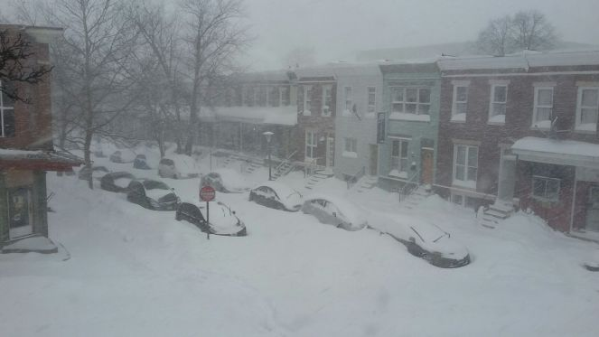 a street of Baltimore rowhomes covered in snow
