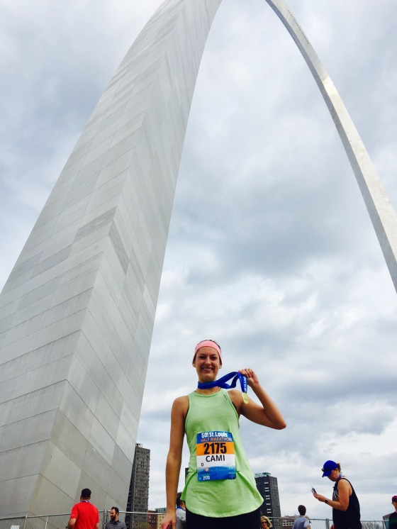 Cami standing underneath the St. Louis Arch holding a completion medal for the half marathon