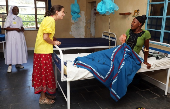 a doctor smiling at a patient sitting on a bed with a blanket on her lap