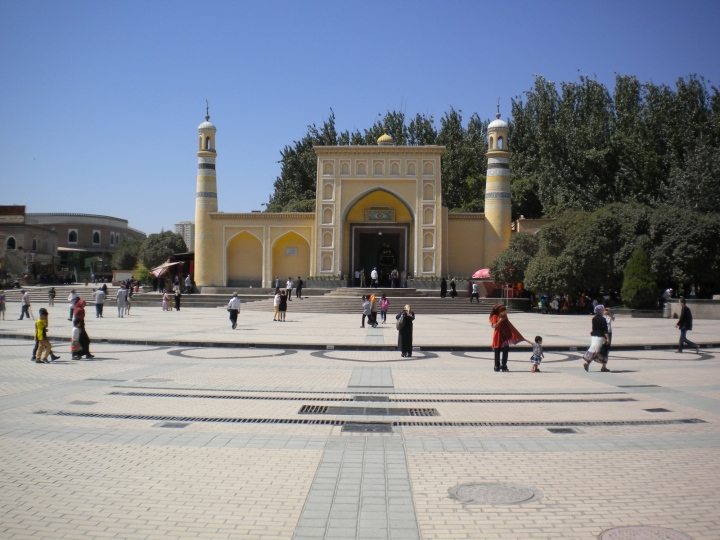 a yellow mosque with a huge open space in front of it