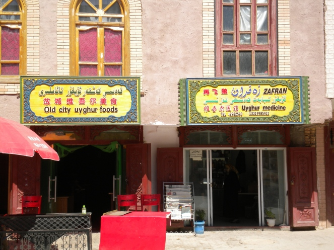 shops with signage in English, Chinese, and Uygher