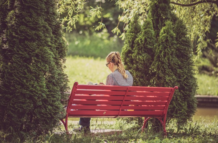 A woman sitting on a park bench reading a book