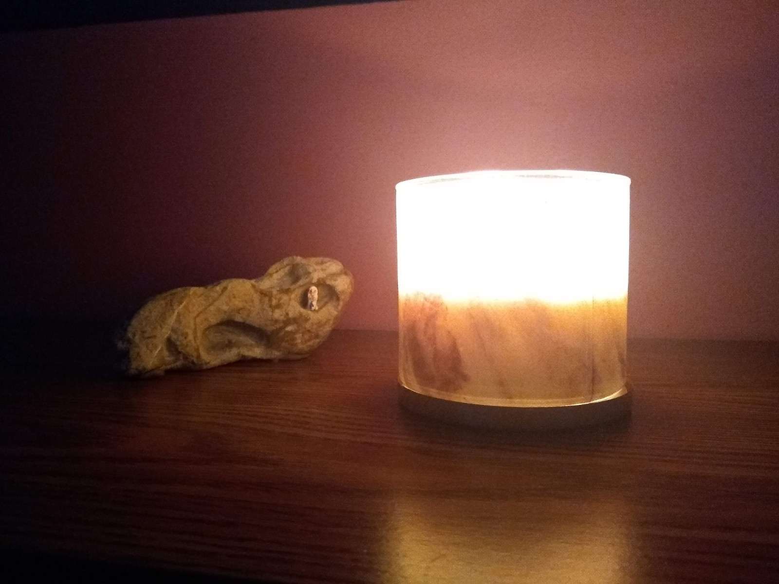 a decorated rock and a lit candle upon a wooden table