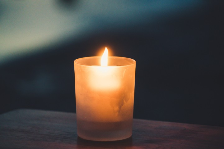 A burning candle resting on a brown table