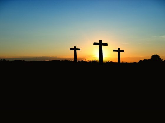 Three crosses silhouetted by a rising sun