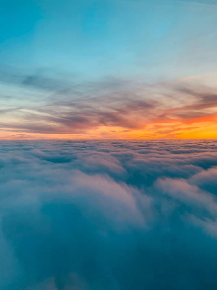a photo of a sunset taken from just above the clouds