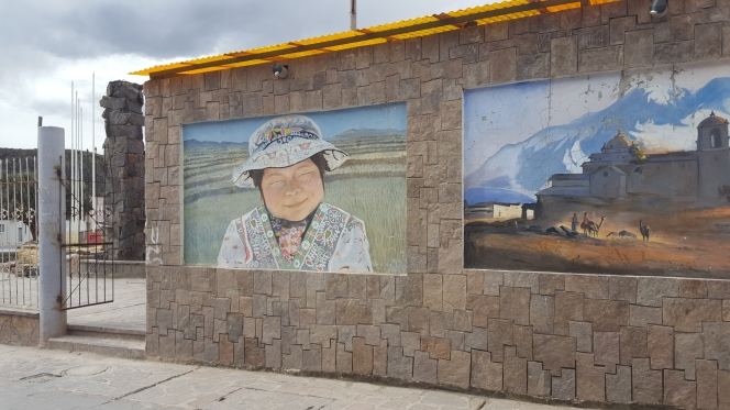 an outdoor stone wall with artwork of a smiling woman on it