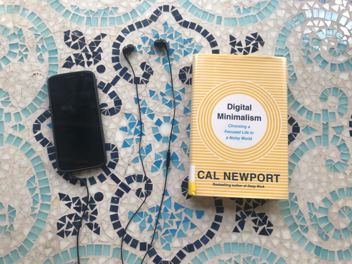 Cal Newport's book Digitial Minimalism next to a smartphone with headphones attached