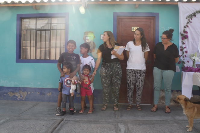 JVs and Peruvian children standing in front of a house. Most of the people are looking to something off to the right.