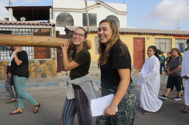 two JVs smiling walking down a street in Peru with others walking behind them
