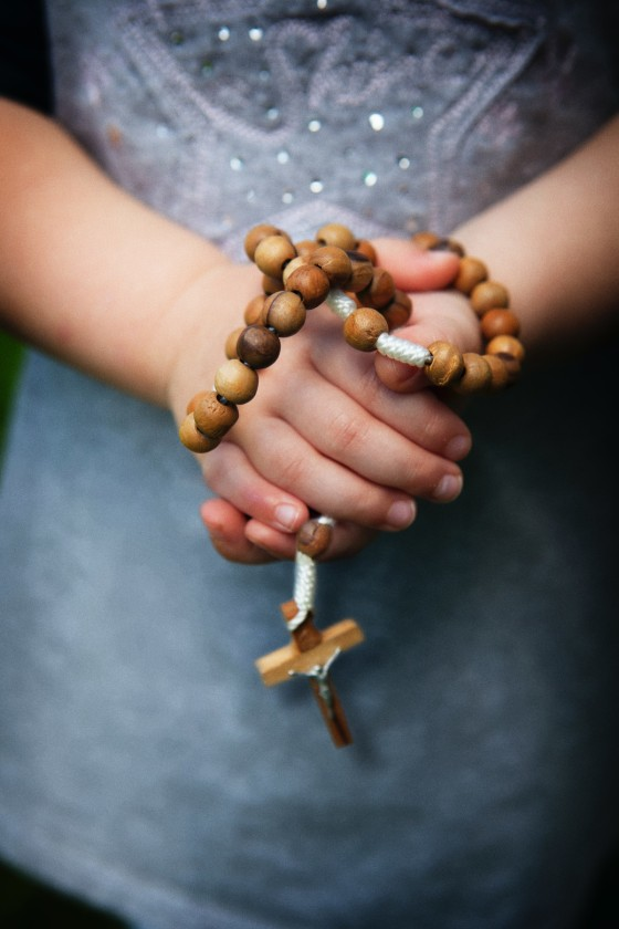 a person's hands folded in prayer holding a rosary