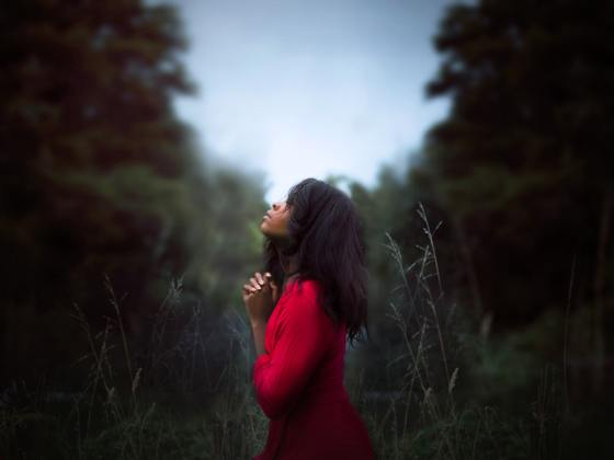 a woman standing between trees praying with her hands folded together and looking upward